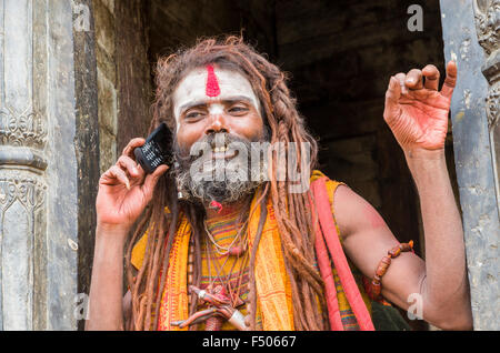 Sadhu, Holy Man, using his mobile phone opposite the burning ghats near Pashupatinath Temple - Stock Photo
