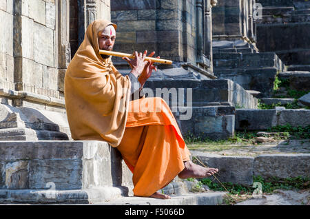 Young man playing flute at the burning ghats near Pashupatinath Temple - Stock Photo