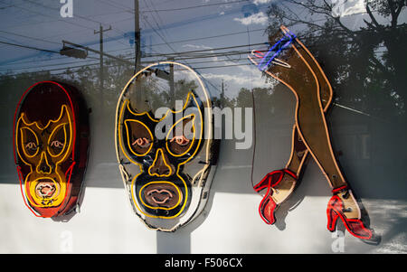 Neon signs of luchadores and legs at the Roadhouse Relics art gallery in Austin, Texas - Stock Photo