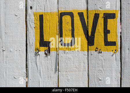The word 'LOVE' written on a whitewashed fence - Stock Photo