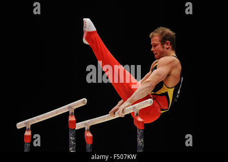 FABIAN HAMBUECHEN from Germany competes on the parallel bars during the preliminary round of the 2015 World Gymnastics - Stock Photo