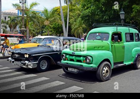 Cuban vintage taxis waiting at a zebra crossing in Old Havana Cuba - Stock Photo