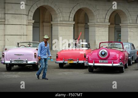 Cuban city cowboy walking across the plaza with parked vintage tourist taxis and colonnades - Stock Photo