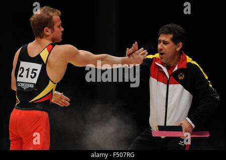 FABIAN HAMBUECHEN from Germany celebrates with his coach after his parallel bars routine during the preliminary - Stock Photo