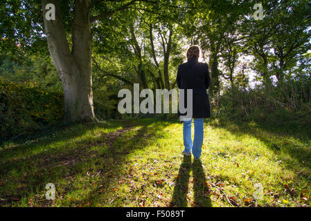 Woman standing among trees with sunlight behind her. - Stock Photo