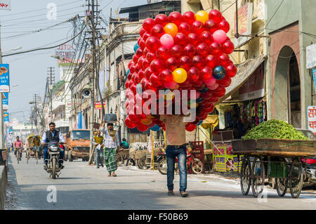 Man carrying a huge pack of red toy balls along a street - Stock Photo