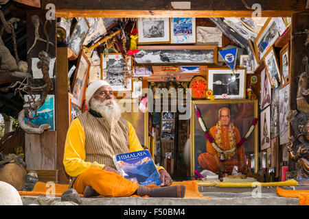 Swami Sundaranand, a famous Sadhu, yogi and photographer, is sitting in front of his house and displaying his book - Stock Photo