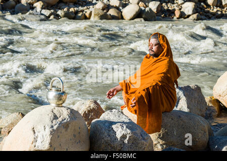 A Sadhu, holy man, is sitting on a rock and meditating at the banks of the river Ganges - Stock Photo