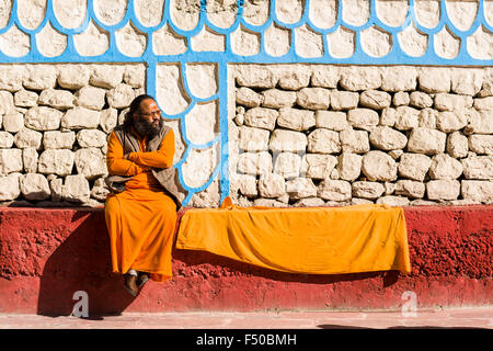 A Sadhu, holy man, is sitting on a wall at the banks of the river Ganges - Stock Photo