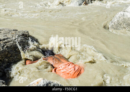 A Sadhu, holy man, is taking bath in the freezing cold water at Gaumukh, the main source of the holy river Ganges - Stock Photo