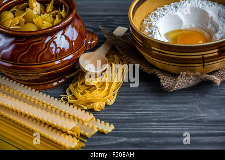 Pasta mix, ceramic bowl with meal and eggs on dark wooden table background - Stock Photo