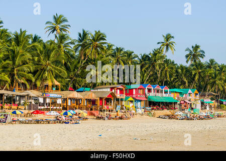 Colorfully painted huts at Palolem Beach with blue sky, palmtrees and white sand - Stock Photo