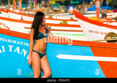 A young woman, wearing bikini, is posing for photographs in front of a fishing boat at Palolem Beach - Stock Photo