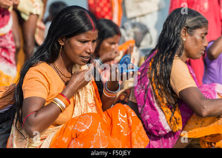 A group of female pilgrims, women, are applying tilaks after taking bath and praying in the holy river Yamuna - Stock Photo