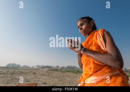 One female pilgrim, woman, is praying after taking bath in the holy river Yamuna - Stock Photo