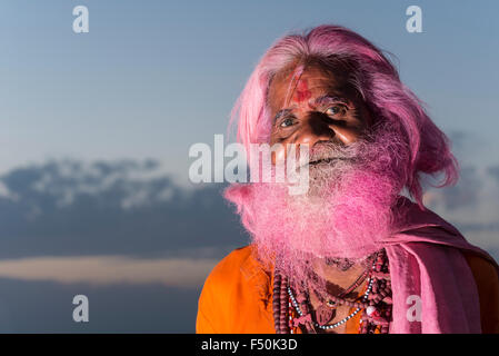 Portrait of an old man, who got his usually grey beard colored pink at Holi festival - Stock Photo