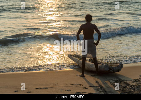 A fisherman is waiting for the right moment to start beside his boat on the beach - Stock Photo