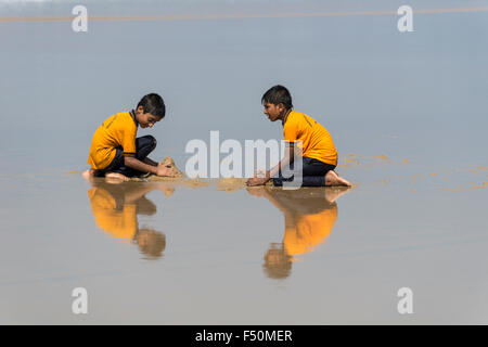 Two schoolboys, wearing yellow shirts, are playing with sand on the beach, mirroring in the water - Stock Photo