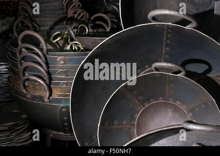 Many different iron pans and pots are for sale in a smiths little shop in the market - Stock Photo