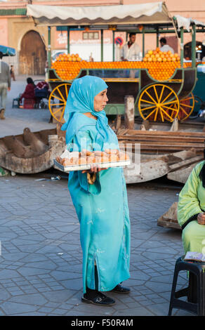 Local Muslim woman in blue jilbab holding a tray of cakes, Jamaa el Fna square, Medina quarter, Marrakesh, Morocco, - Stock Photo