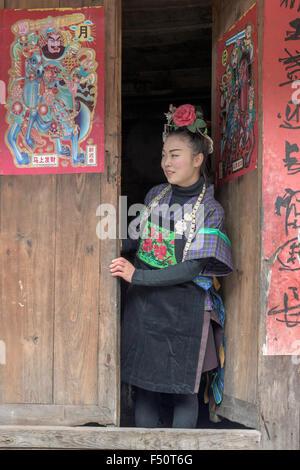 Green Medium Skirt Miao girl in a doorway, Shiqiao Village, Guizhou Province, China - Stock Photo