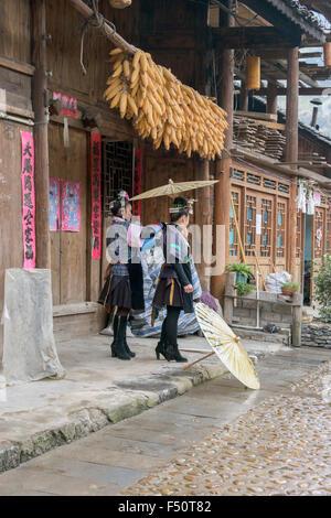 Green Medium Skirt Miao girls on a rainy day, Shiqiao Village, Guizhou Province, China - Stock Photo