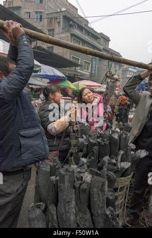 Weighing a basket of charcoal with a traditional Chinese scale, Rongjiang, Guizhou Province, China - Stock Photo