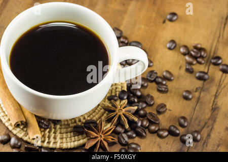 coffee on the cup with coffee beans and cinnamon sticks on wood background, warm toning, selective focus - Stock Photo