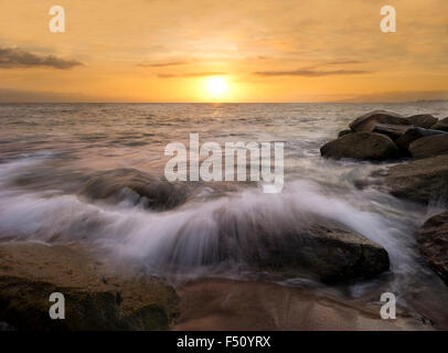 Ocean sunset is waves rushing over sand on rocks along the beach as the sun sets in a colorful soft cloud filled - Stock Photo