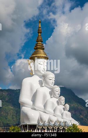 White Buddha statue amidst the mountains in Thailand, wat phasornkaew - Stock Photo