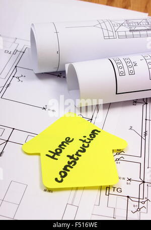 house of yellow paper with text home construction and rolls of diagrams lying on electrical construction - Home Construction Diagram