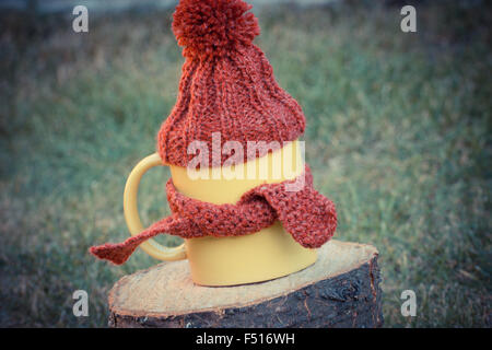 Vintage photo, Yellow cup of hot tea with woolen cap wrapped woolen scarf on wooden stump in garden, warming beverage - Stock Photo