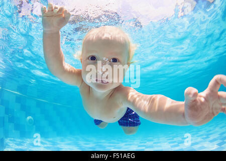 Funny face portrait of little baby boy having a water exercises - swimming and diving underwater with fun in the - Stock Photo
