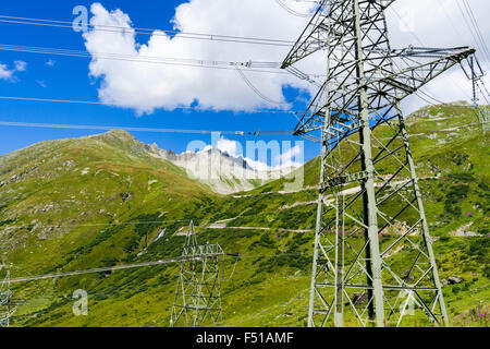An electricity line is crossing green mountains slopes in high altitude - Stock Photo