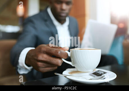 Close up shot of young man 's hand picking up cup of coffee. Businessman sitting at hotel lobby drinking coffee. - Stock Photo