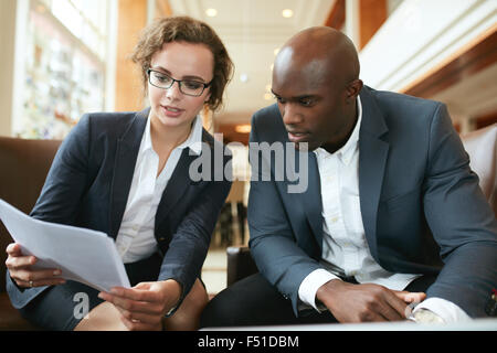 Two business partners sitting together and discussing contract documents. Business executives going through papers - Stock Photo