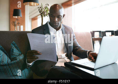 Image of young businessman sitting a hotel coffee shop reading a document while working on laptop. Preparing himself - Stock Photo