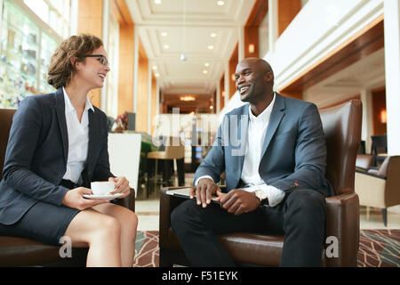 Portrait of happy young businesswoman in meeting with business partner at hotel lobby. Business people having a casual talk duri