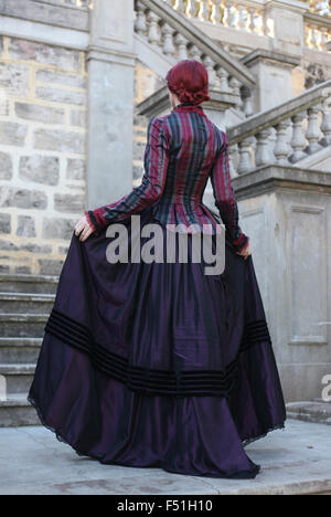 Portrait of a beautiful red haired girl wearing  Gothic inspired Victorian era clothes. - Stock Photo
