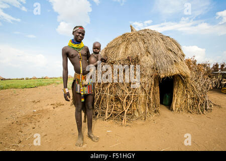 Young Nyangatom woman with baby in arms, stands next to her thatch hut. Omo Valley, Ethiopia - Stock Photo