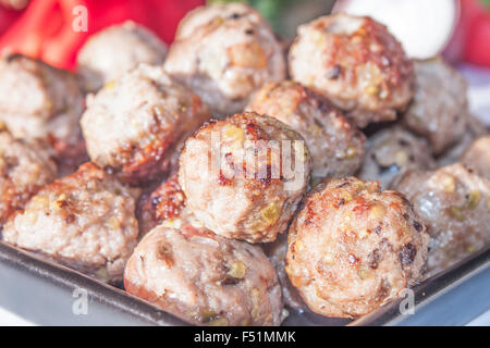 A pile of meat balls on a black plate, in front of vegetables - Stock Photo