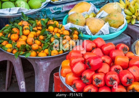 A lot of fresh red persimons, Diospyros discolor, at a market in Phu quoc, Vietnam - Stock Photo