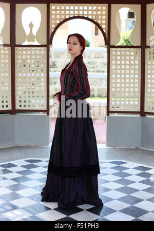 portrait of a beautiful red haired girl wearing Gothic inspired Victorian era clothes. vampire or historical romance - Stock Photo