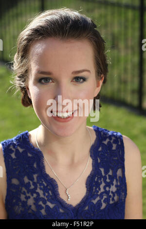 Portrait of a young woman in a blue dress smiling. - Stock Photo