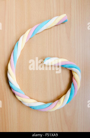Colorful twisted marshmallow on a wooden background as a G letter - Stock Photo