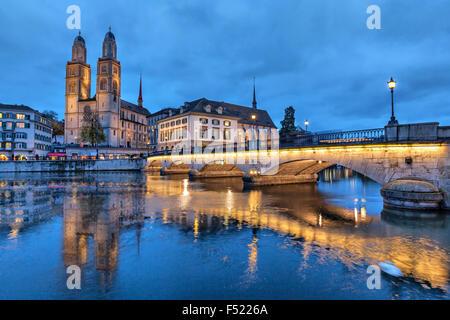 Munsterbrucke and Grossmunster church reflecting in river Limmat, Zurich, Switzerland - Stock Photo