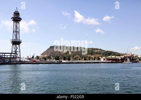 Viewed from across Port Vell, the Montjuic hill and Cable Car tower in Barcelona, Spain. - Stock Photo