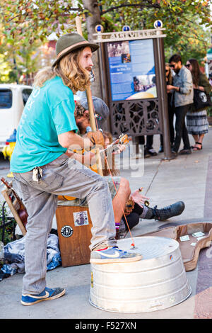 Street musicians busk in front of Pritchard Park in Asheville, North Carolina. - Stock Photo