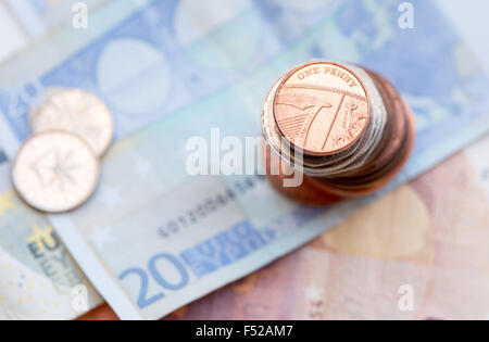 British one penny coin on a pile of coins and 20 Euro note - Stock Photo