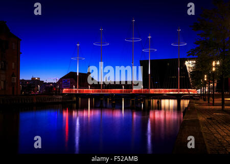 The Circle Bridge spanning Christianshavn Canal at sunset, The Black Diamond in the background, Copenhagen, Denmark - Stock Photo